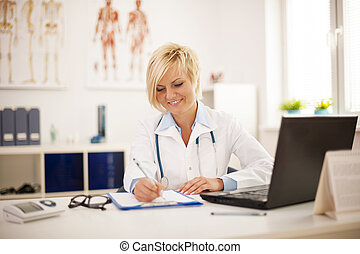 Beautiful young female doctor working at her office
