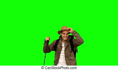 Cheerful man raising his hat on green screen in slow motion