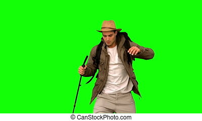 Man wiping his forehead while he is trekking on green screen...