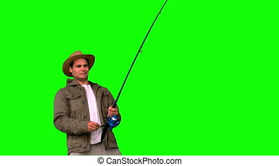 Man making effort while fishing on green screen in slow...