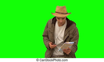 Man orienteering with a map and a compass on green screen in...