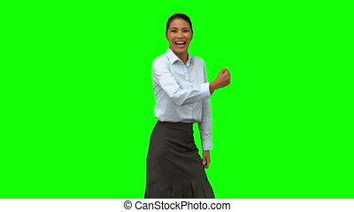 Cheerful businesswoman gesturing on green screen in slow...
