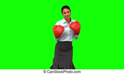 Businesswoman with boxing gloves hitting on green screen in...