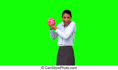 Businesswoman shaking a full piggy bank on green screen in...