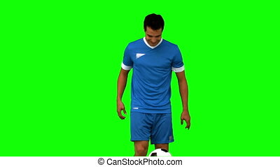 Man juggling a football on green screen in slow motion