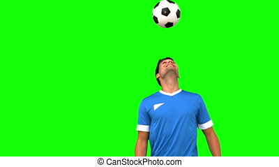 Man juggling a football with his head on green screen in...
