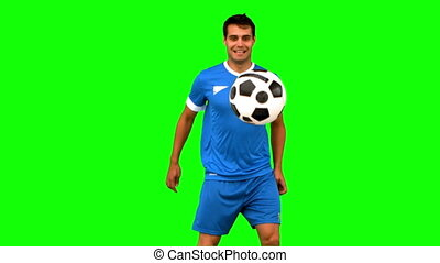 Handsome man juggling a football on green screen in slow...