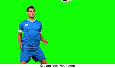 Attractive man juggling a football on green screen in slow...