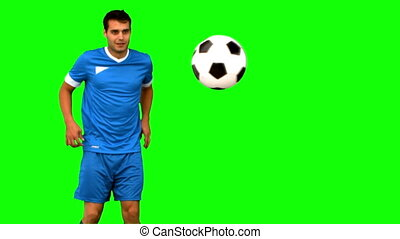 Man playing with a football on green screen in slow motion