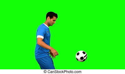 Handsome man playing with a football on green screen in slow...