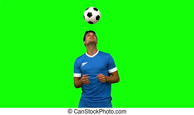 Man juggling a football with head on green screen in slow...