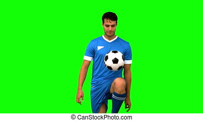 Man juggling a football with his knee on green screen in...