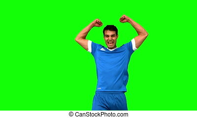 Happy football player raising arms on green screen in slow...