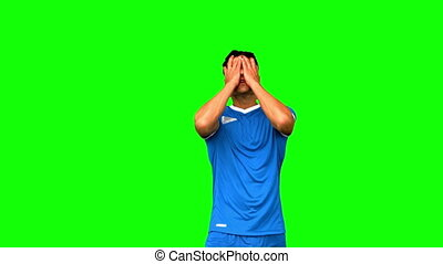 Angry football player holding his head on green screen in...