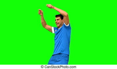 Happy football player gesturing aft
