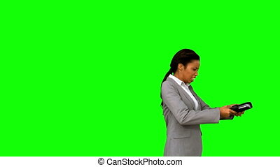 Angry businesswoman throwing her agenda on green screen in...