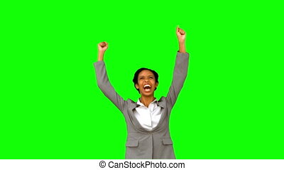 Pretty businesswoman raising arms on green screen in slow...