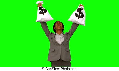 Businesswoman holding money bags on green screen in slow...