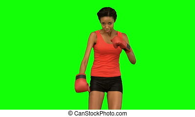 Woman performing high kick on green screen in slow motion