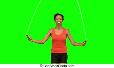 Woman working out with a rope on green screen in slow motion