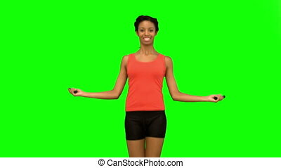 Cheerful woman working out with a rope on green screen in...