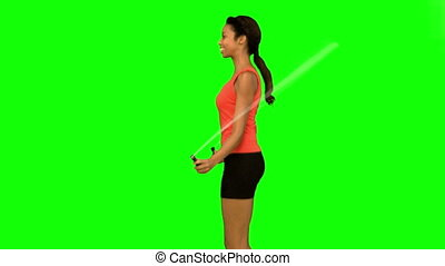 Pretty woman working out with a rope on green screen in slow...