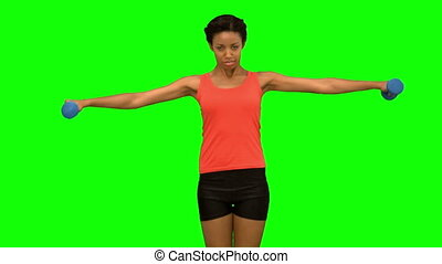 Pretty woman lifting dumbbells on green screen in slow...