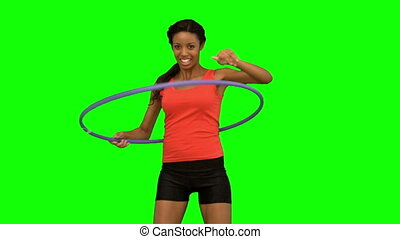 Woman playing with a hula hoop on green screen in slow...
