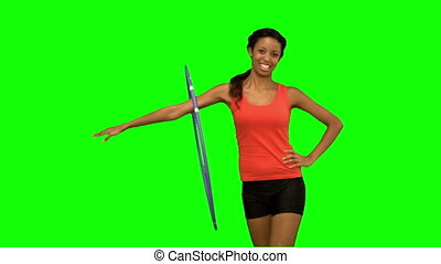 Woman working out with a hula hoop on green screen in slow...