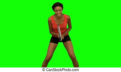 Woman playing tennis on green screen in slow motion