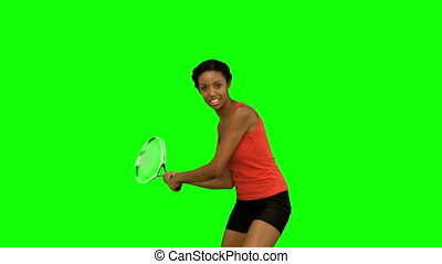 Pretty woman playing tennis on green screen in slow motion