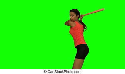 Pretty woman playing baseball on green screen in slow motion