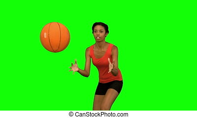 Woman catching and throwing a basketball on green screen in...