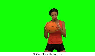 Pretty woman playing basketball on green screen in slow...