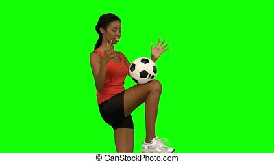 Woman juggling a football on green screen in slow motion