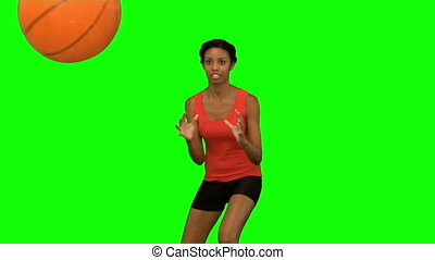 Pretty woman catching and throwing a basketball on green...