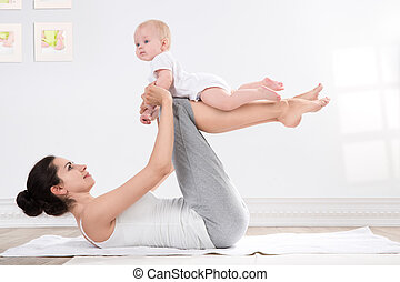 mother and baby gymnastics - young mother does physical yoga...