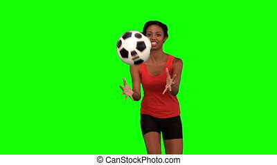 Woman catching a football on green screen in slow motion