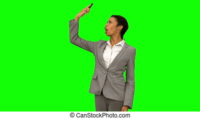 Angry woman raising her phone in the air on green screen in...