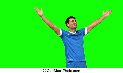 Football player waving a kissing at people on green screen...