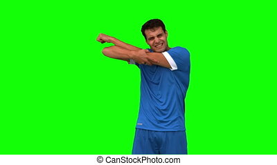 Football player suffering from arm injury on green screen in...