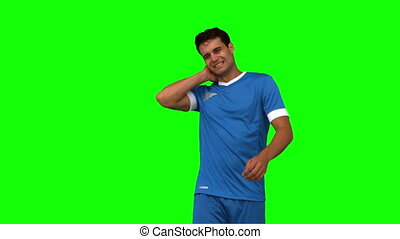 Football player suffering from neck pain on green screen in...