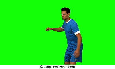 Football player kicking a football on green screen in slow...