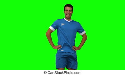 Football player warming up on green screen in slow motion