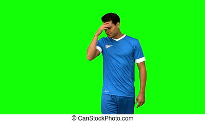 Sad football player holding his head on green screen in slow...