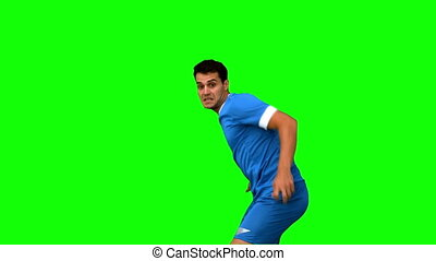 Handsome football player warming up on green screen in slow...