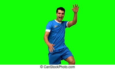 Football player celebrating a goal on green screen in slow...