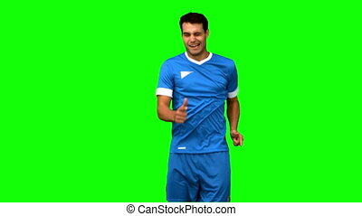 Happy football player celebrating a goal on green screen in...