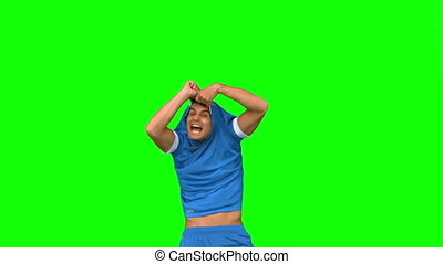Handsome football player celebrating a goal on green screen...