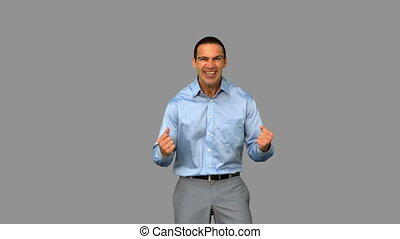 Cheerful businessman gesturing on grey screen in slow motion
